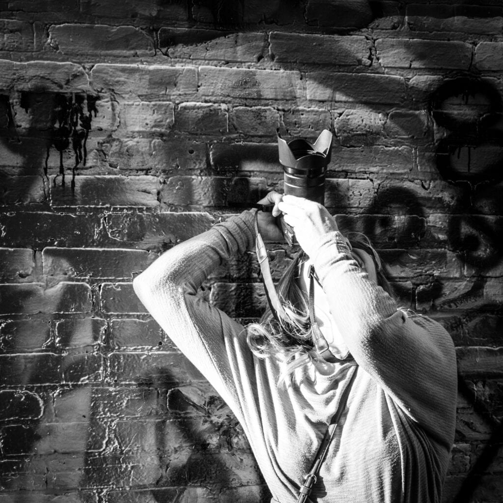 Black and white photo of a photographer looking up for a shot. Her arms are angled and camera pointed up. The setting is Graffiti Alley in Baltimore where other artists have left their artistic mark on the walls.