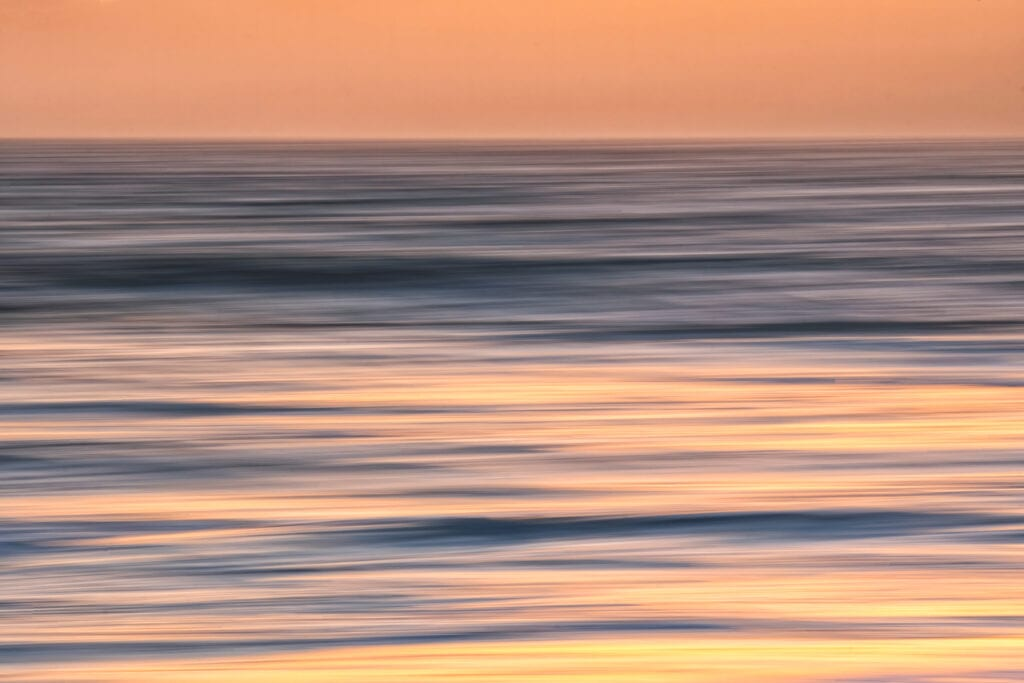 Abstract ocean sunset with calm waves and orange glow on blue water.