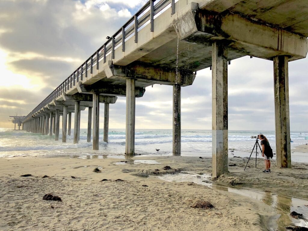 Scripps Pier Photo Shoot in San Diego with ocean waves crashing at the pillars.