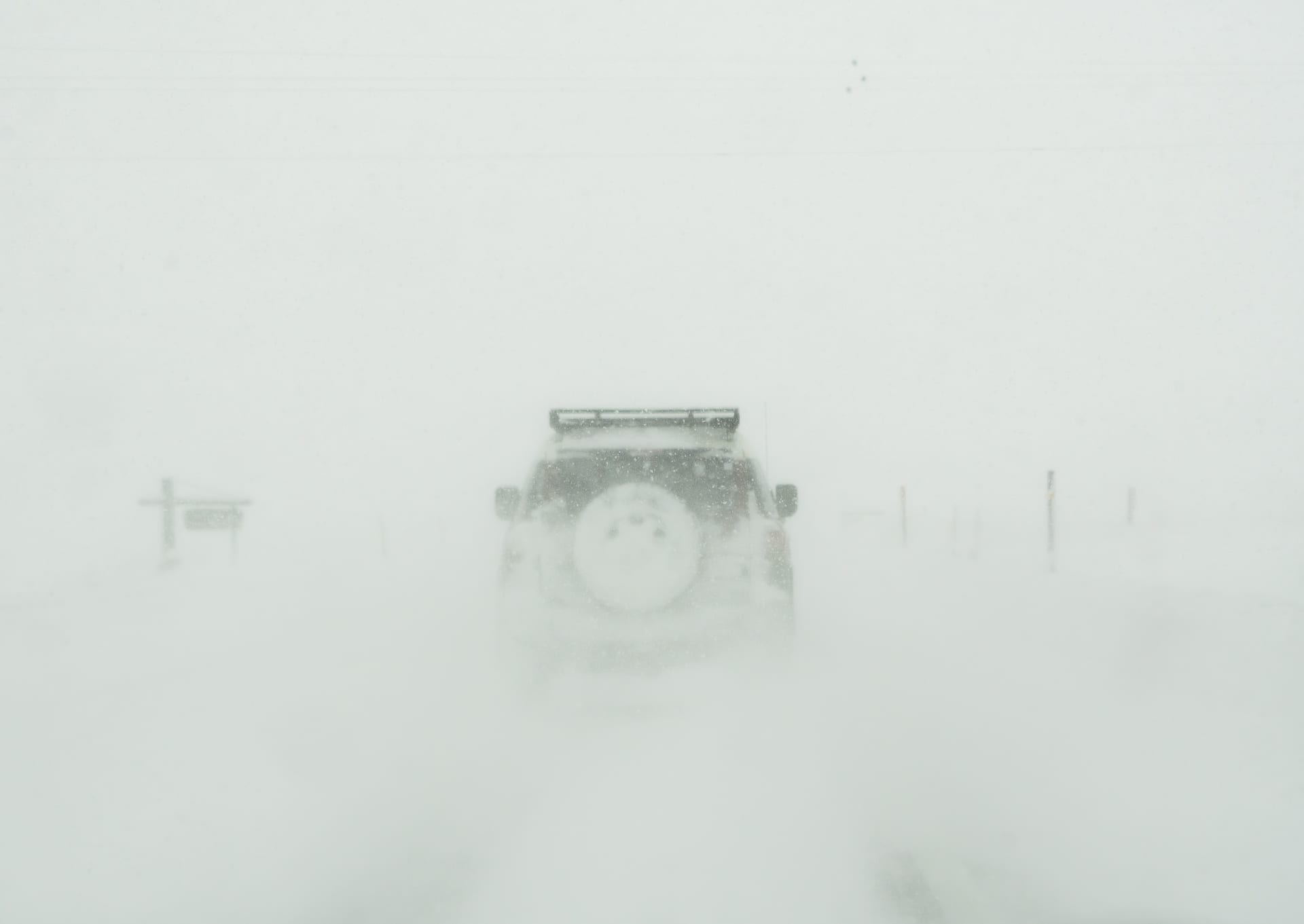 Ground blizzard driving with car in front.