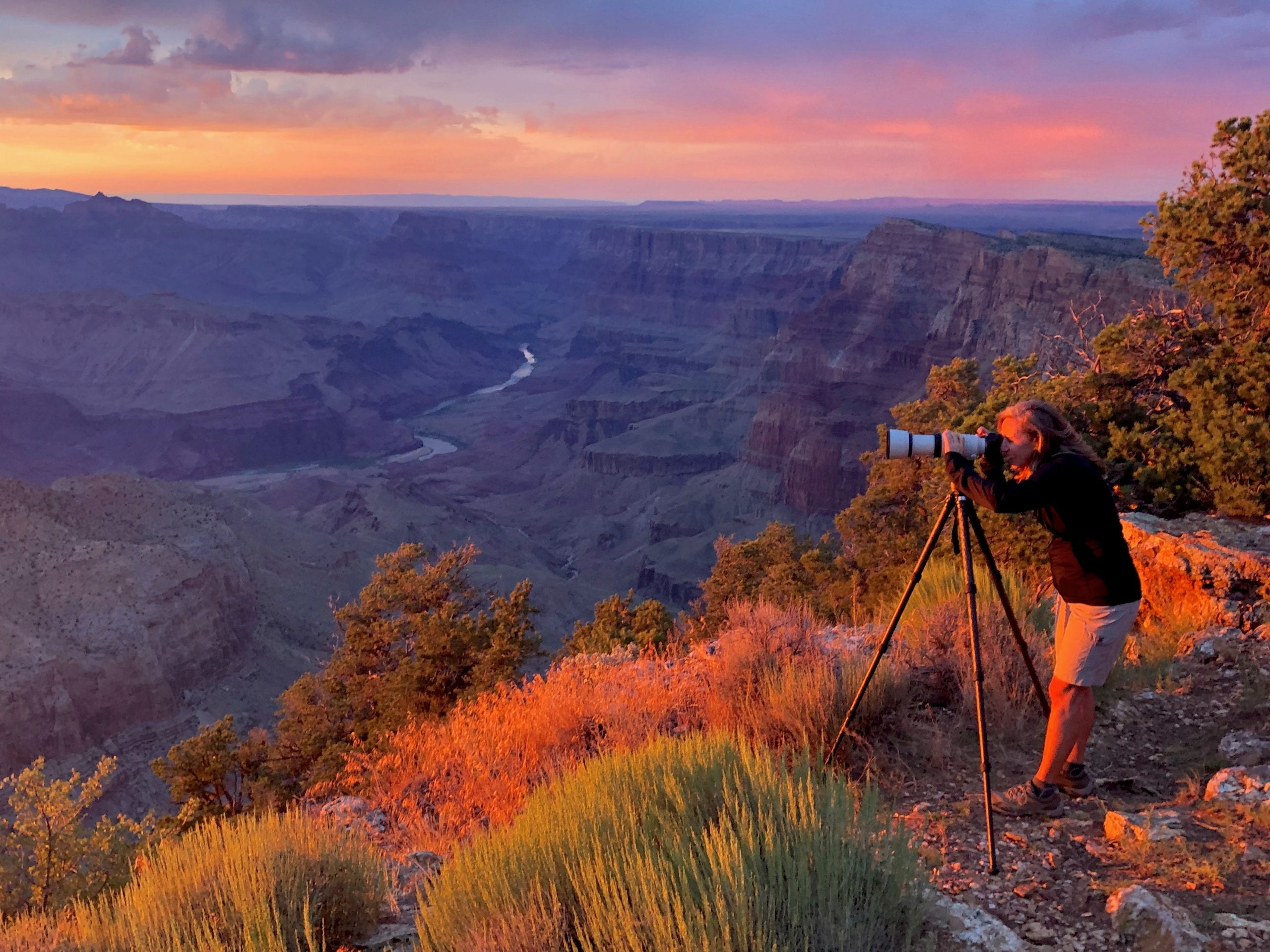 Photographer taking a picture of sunset at the Grand Canyon.