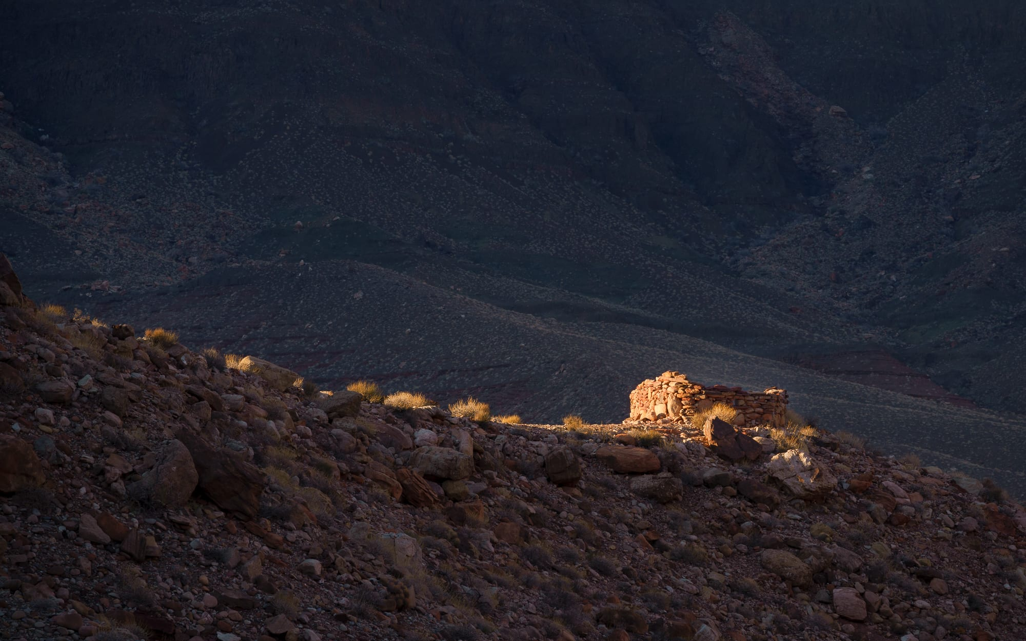 Sunlight hits the hilltop and lights up an ancestral Pueblo structure in the Grand Canyon