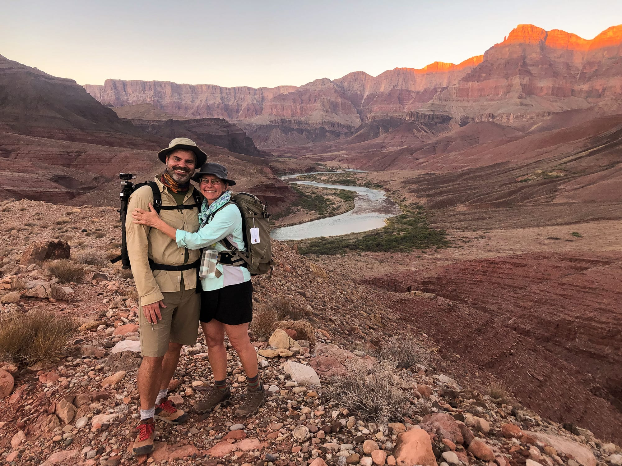 Two hikers on the Escalante Trail at sunset overlooking the Cardenas Camp and Colorado River in the Grand Canyon.